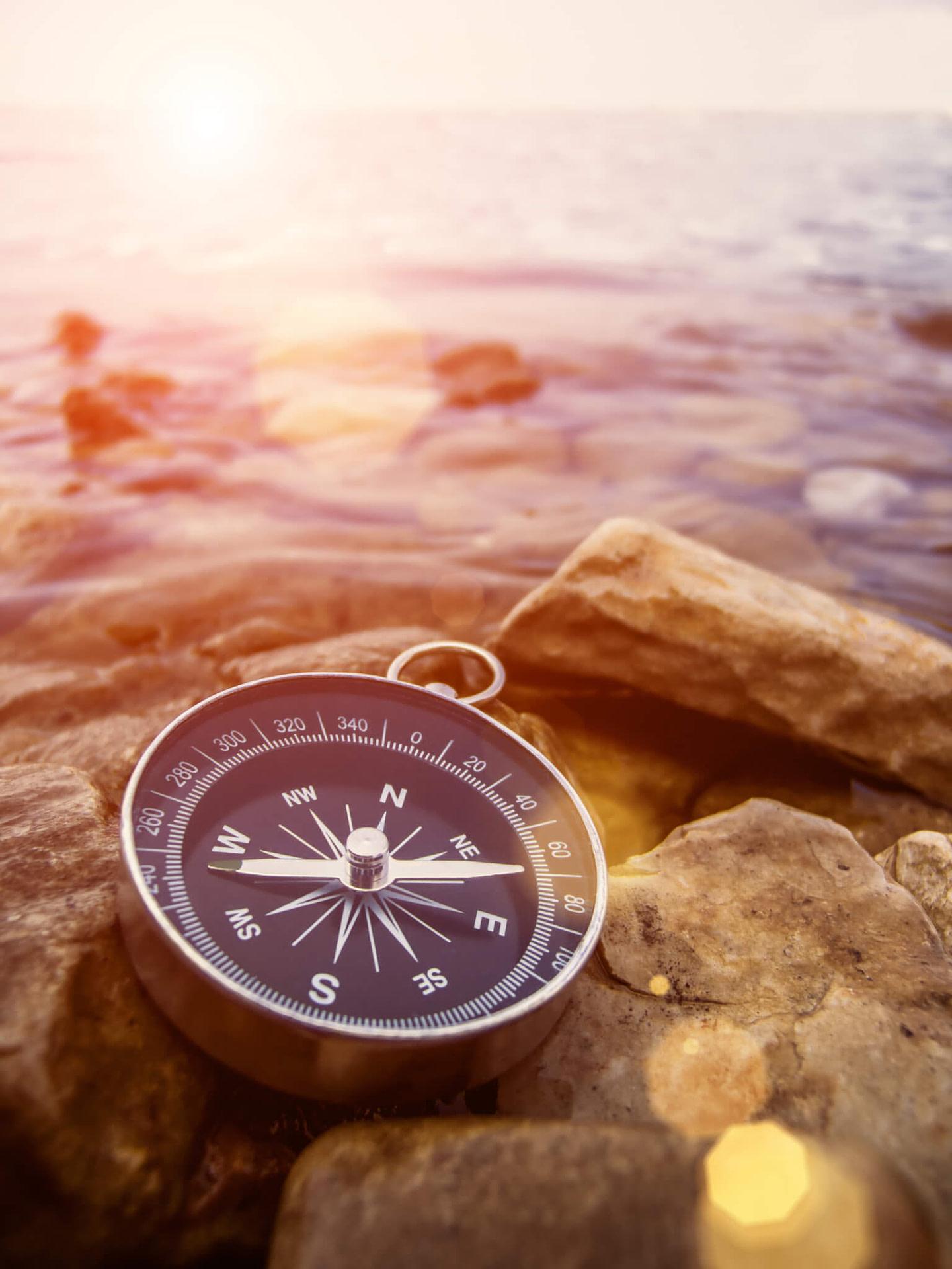 Kompass am Strand bei Sonnenuntergang am Horizont.