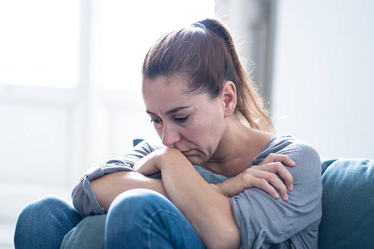 Braunhaarige Frau sitzt traurig im Wohnzimmer