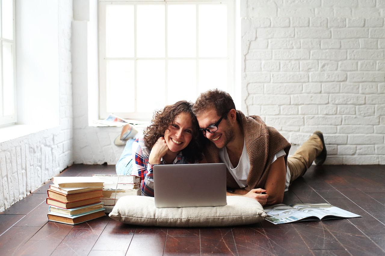 Ein zufriedenes Paar vor ihrem Laptop im Wohnzimmer.