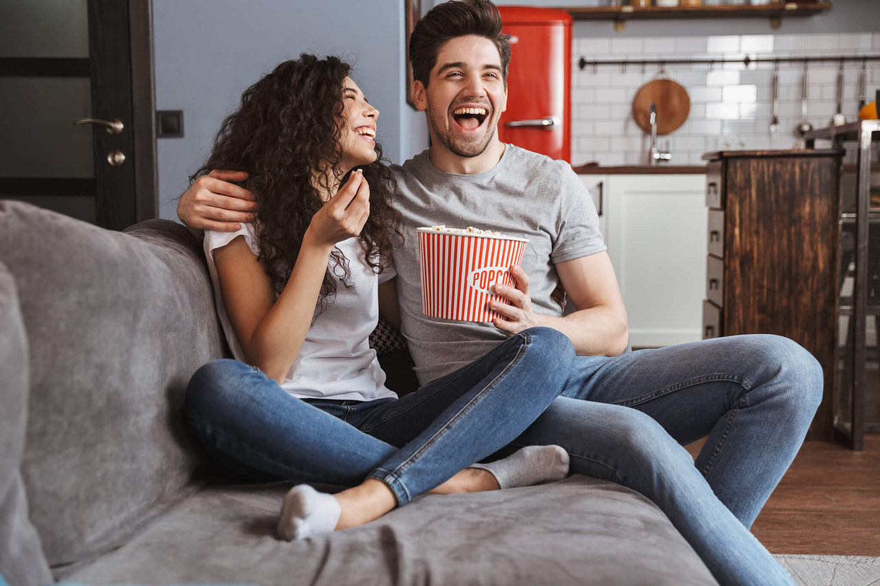 Junges Paar lachend auf dem Sofa sitzend.